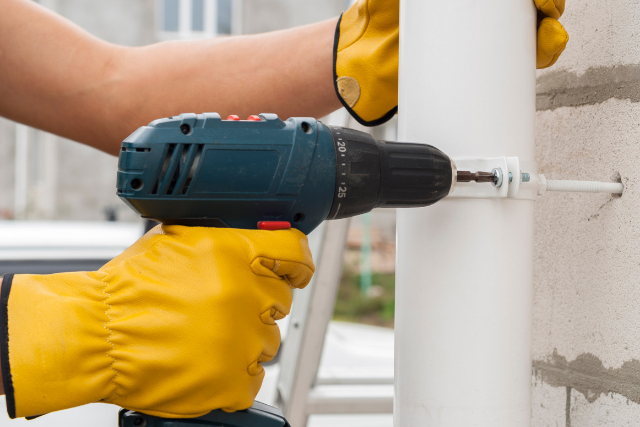 Installation of gutter system by worker with drill