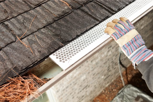 Gutter guard installation by a worker with gloves on